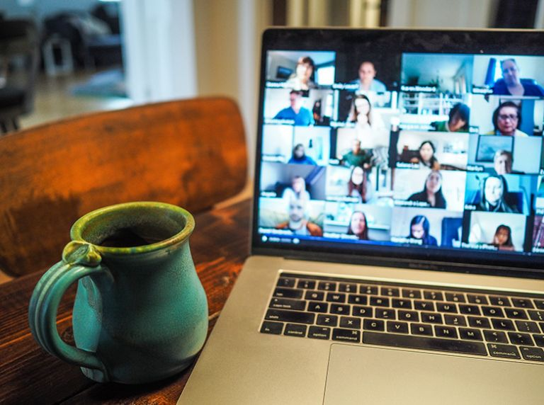 Laptop video conference call and coffee cup