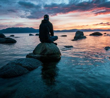 sitting on rock in lake