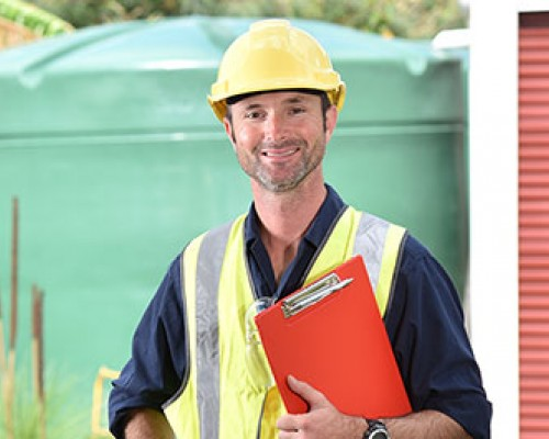 Man holding clipboard with hard hat